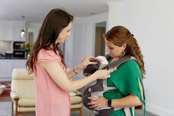 A female wearing a baby carrier with a baby in it. Another female is adjusting the baby carrier