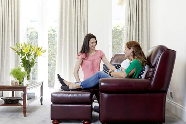 A female is sitting on an armchair with a baby. Another female is kneeling and talking to her