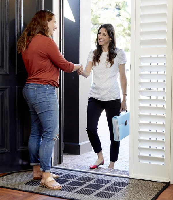 2 females shaking hands whilst standing at the front door to a house. They are smiling.