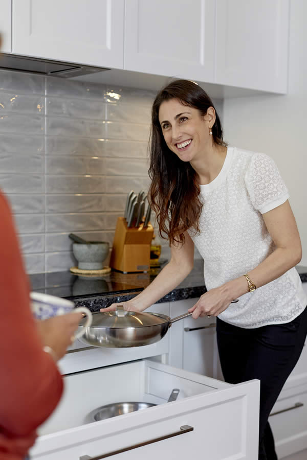 A female in a kitchen holding a frypan smiling at someone out of view